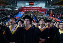 Students from the Huazhong University of Science and Technology singing during their graduation ceremony in a sports stadium in Wuhan City, in China's central Hubei province, on June 20, 2017. (STR/AFP/Getty Images)