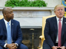 Watched by Senator Tim Scott (R-SC) President Donald Trump speaks during a working session regarding opportunity zones following the recently signed tax bill in the Oval Office of the White House in Washington, DC on Feb. 14, 2018.(MANDEL NGAN/AFP/Getty Images)