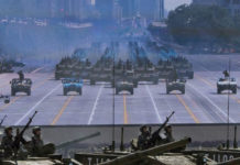 Soldiers in tanks pass in front of a screen near Tiananmen Square during a military parade in Beijing on Sept. 3, 2015. (Kevin Frayer/Getty Images)