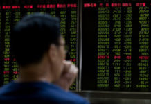 A man sitting in front of a screen showing stock prices at a securities brokerage in Beijing. (Nicolas Asfouri/ AFP/Getty Images)