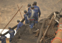Mine workers carry pipes to the entrance to the Wangjialing coal mine during the Wangjialing coal mine flood incident in 2010. (Source: CNN)