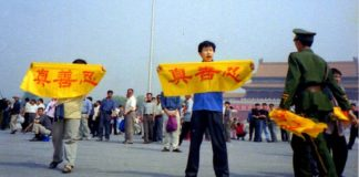 """A Falun Gong practitioner holds a banner at Tiananmen Square reading """"Truth, Compassion, Tolerance,"""" the core tenets of the practice. A policeman approaches to arrest him. (Image: Falun Dafa Information Center)"""