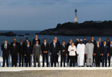 G-7 leaders and guests pose for a family picture with the Biarritz lighthouse in the background on the second day of the annual G-7 summit: (First row) L-R Britain's Prime Minister Boris Johnson, South Africa's President Cyril Ramaphosa, Rwanda's President Paul Kagame, African Union Chair Egyptian President Abdel Fattah el-Sisi, Japan's Prime Minister Shinzo Abe, Canada's Prime Minister Justin Trudeau, US President Donald Trump, France's President Emmanuel Macron, Germany's Chancellor Angela Merkel, Senegal's President Macky Sall, Burkina Faso's President Roch Marc Christian Kabore, Chile's President Sebastian Pinera, Italy's Prime Minister Giuseppe Conte, European Council President Donald Tusk; (Second row) Chairperson of the African Union Commission Moussa Faki Mahamat (2nd,L), Australian Prime Minister Scott Morrison (4th,L), United Nations Secretary-General Antonio Guterres (6th,R), India's Prime Minister Narendra Modi (5th,R), Spain's Prime Minister Pedro Sanchez (3rd,R), OECD Secretary-General Jose Angel Gurria (2nd,R), African Development Bank president Akinwumi Adesina (R) in Biarritz, France, on Aug. 25, 2019. (Andrew Parsons/Getty Images)