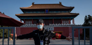 A security guard wearing a facemask amid the concerns over the COVID-19 coronavirus closes a gate outside the forbidden city (back) in Beijing on April 12, 2020. (Nicolas Asfouri/AFP via Getty Images)